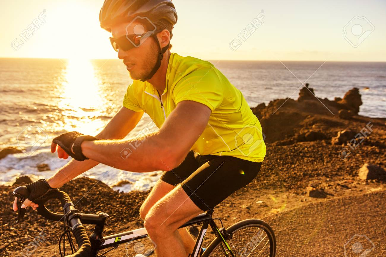 Cyclist biking looking at smartwatch while riding road bike
