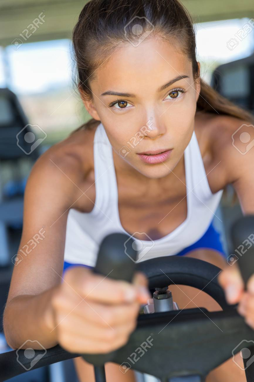 Asian woman training cardio workout at home on indoor bike  Working