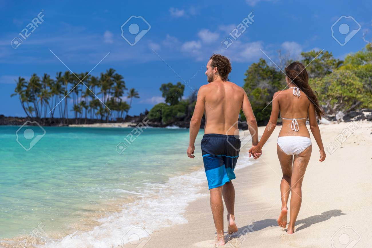 Summer Vacation Suntan Couple Holding Hands Having Fun On Hawaii