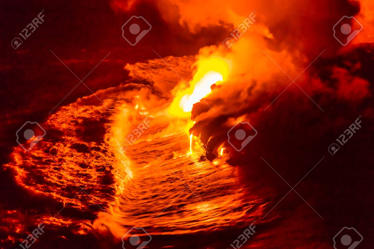 Lava flow pouring into Hawaii ocean at night. Lava falling in ocean waves in Hawaii from Hawaiian Kilauea volcano at night. Molten lava washed by the pacific ocean water crashing in, Big Island, USA. - 99128635