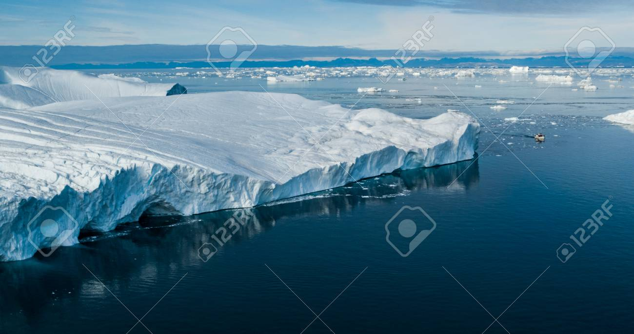Climate Change and Global Warming - Giant Iceberg from melting glacier in Ilulissat, Greenland. Aerial drone of arctic nature landscape famous for being heavily affected by global warming. Boat. - 115505571