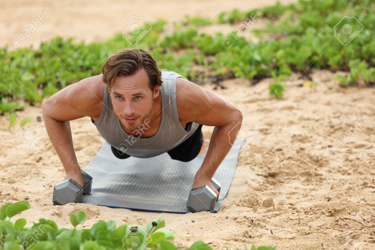 Fitness man doing plank push-ups exercise on dumbbell weights