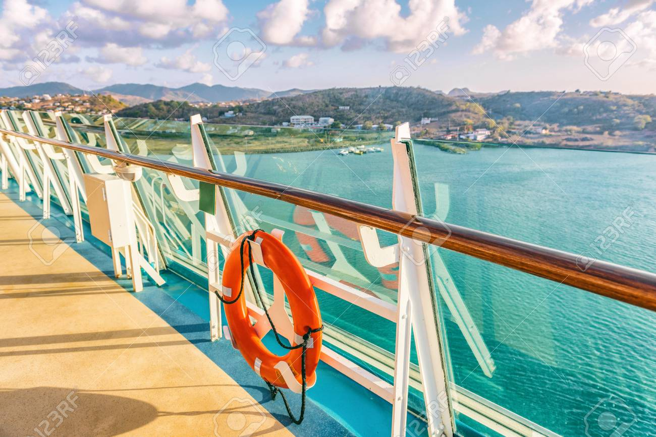 Cruise ship vacation travel Caribbean destination. View of island from boat balcony deck with railing and red lifebuoy. Tropical vacation getaway on sea. - 117964406