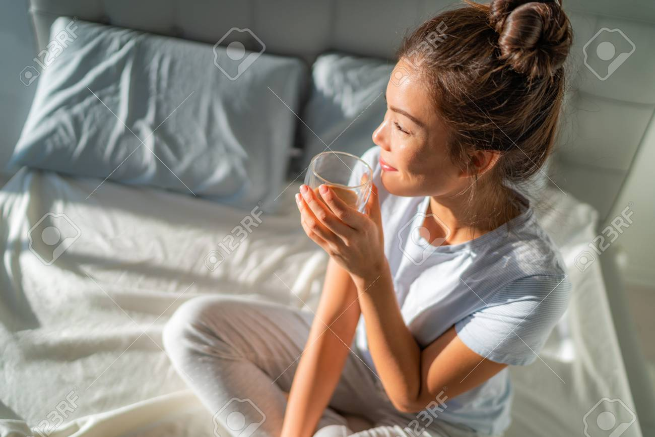 Morning breakfast in bed happy Asian woman drinking hot coffee mug relaxing sitting on mattress. Weekend relaxation wellness. - 118452234