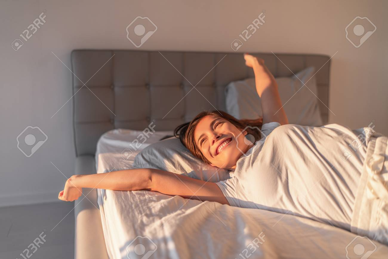 Happy girl waking up in the morning sunshine looking at sunrise sun in window excited to enjoy the day. Wake up energetic Asian woman lying in bed well rested from a good night sleep. - 118452235