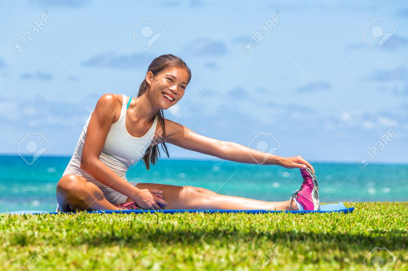 Fitness woman stretch legs doing warm-up before run workout training outdoor. Asian athlete stretching side hamstring muscle yoga stretched leg stretches exercises in outdoor gym. - 122804367