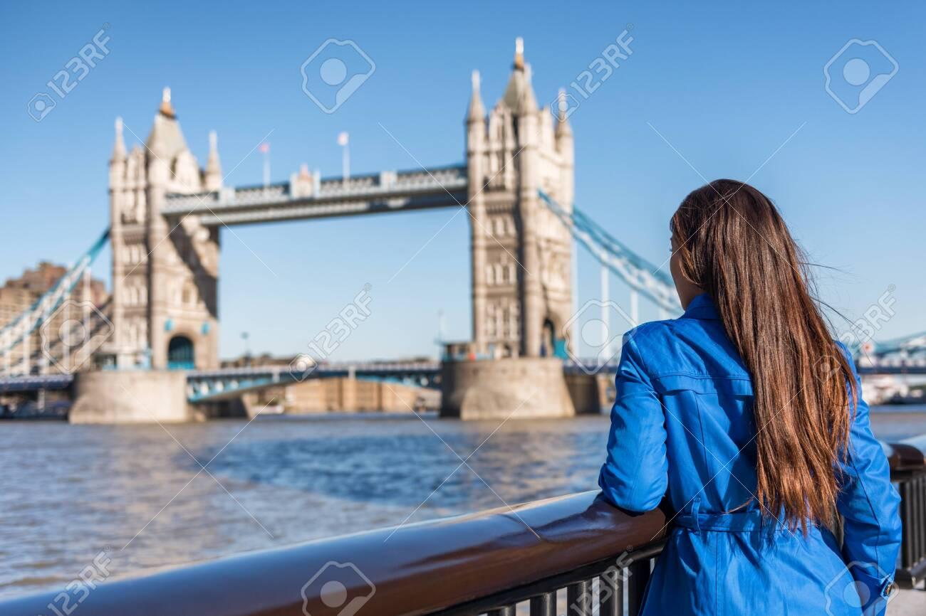 London tourist city travel woman enjoying view of Tower Bridge. Urban lifestyle tourism Europe destination vacation person enjoying view of famous attraction, England, Great Britain, UK. - 122804429