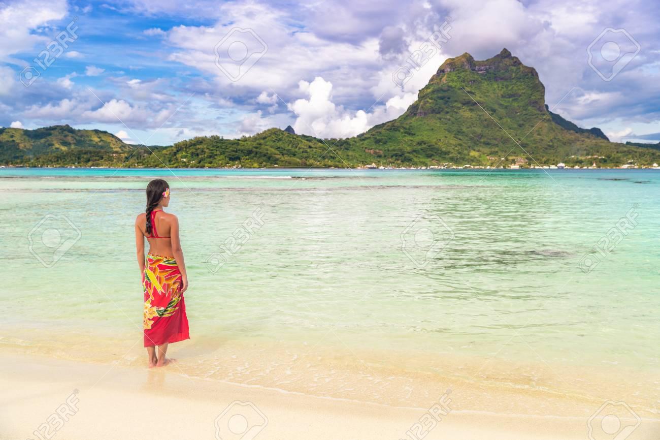ec9dc2ad987 Stock Photo - Tahiti luxury travel beach vacation woman walking in  polynesian cover-up skirt beachwear on idyllic paradise island in French  Polynesia.