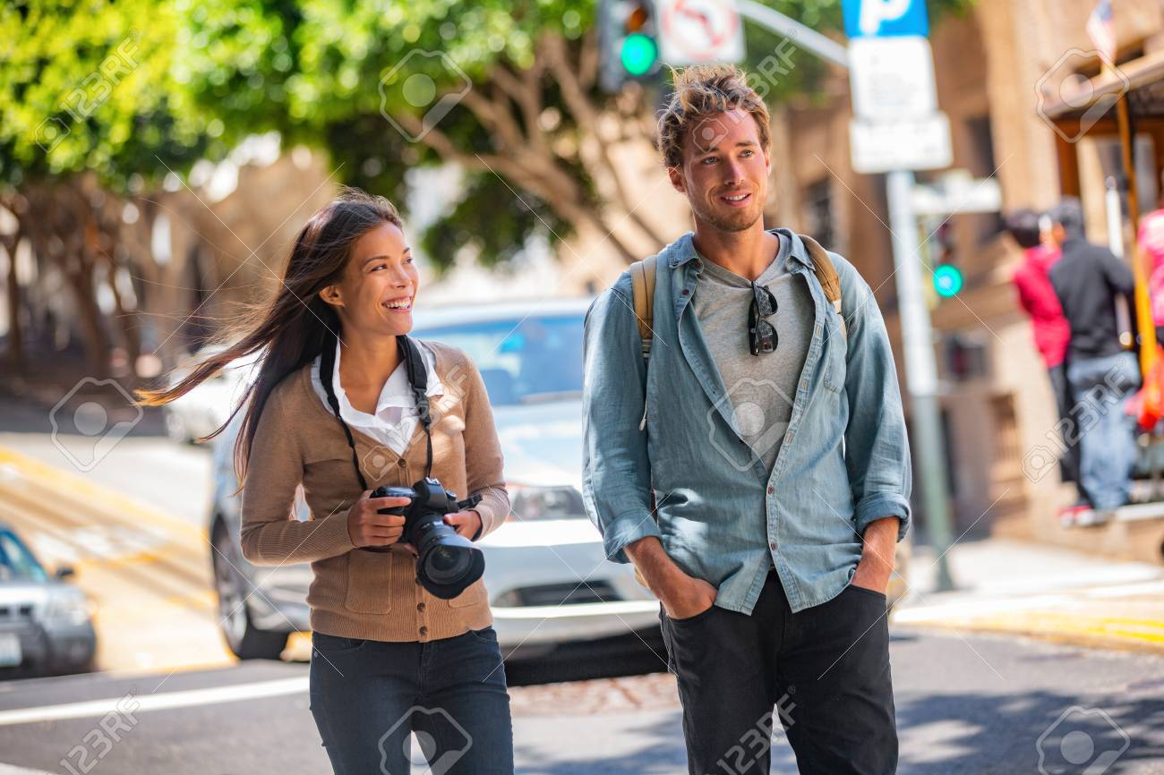 Young students couple tourists walking in city street taking photos with camera on travel. Asian woman, Caucasian man friends urban lifestyle casual. - 122804552
