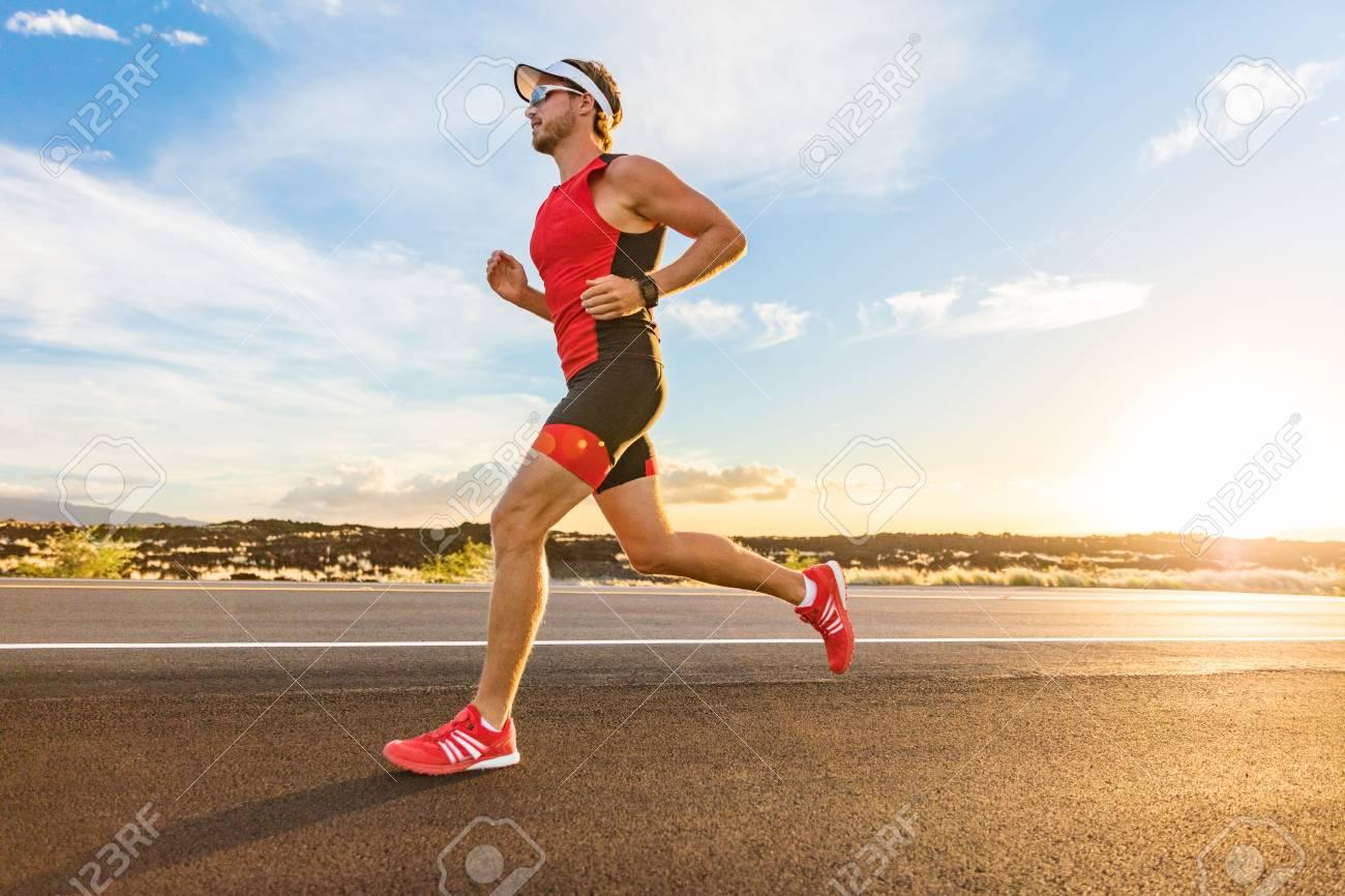 Triathlon - Triathlete man running in triathlon suit training for ironman race. Male runner exercising on Big Island Hawaii. Sunset. - 123633541