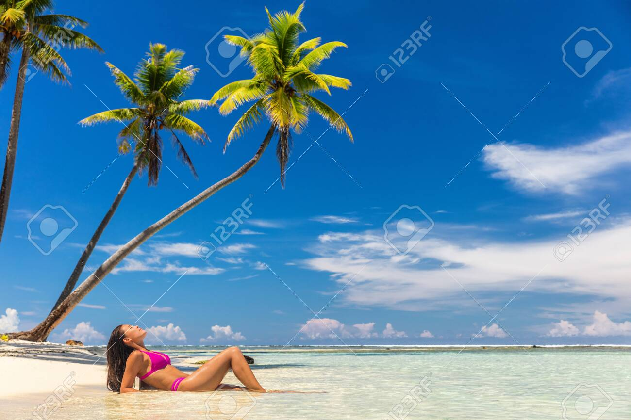 Beach vacation paradise suntan woman relaxing lying down sun tanning in tropical idyllic summer background in Caribbean with blue sky and palm trees. - 124309295