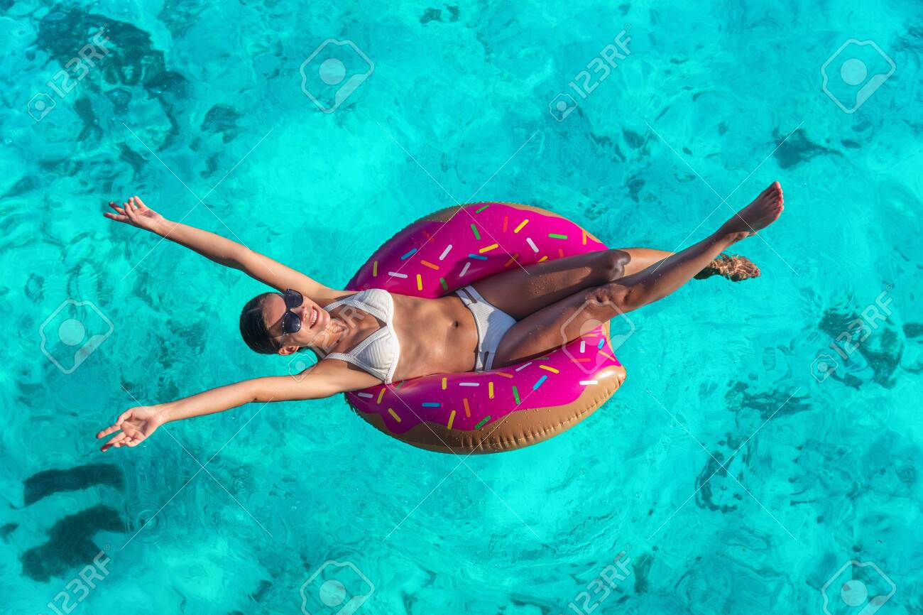 Summer vacation fun woman relaxing in donut swimming pool float..