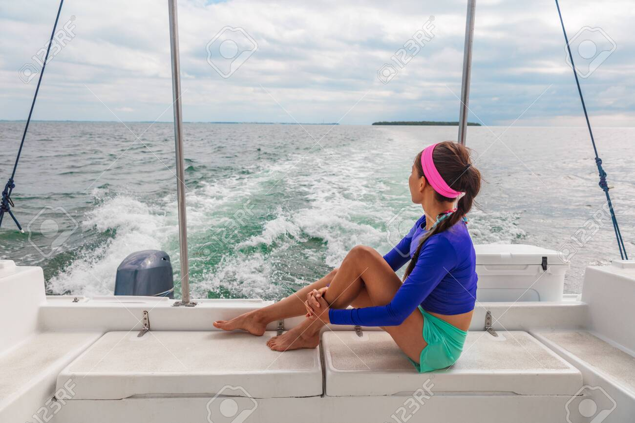 Travel boat excursion tour woman tourist relaxing on deck of motorboat catamaran summer vacation. - 127849867