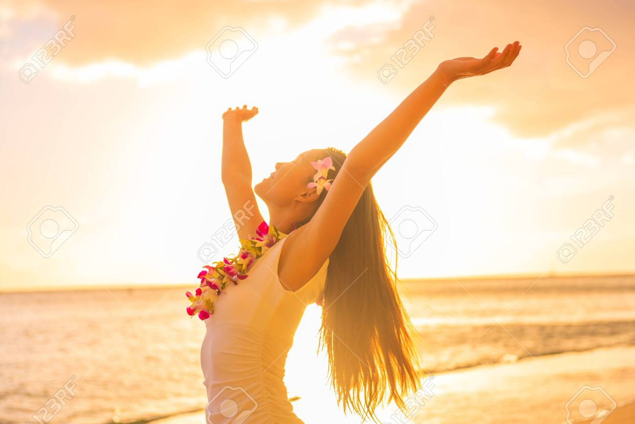 Hawaii hula dancer woman wearing flower necklace lei on sunset beach dancing with open arms free in sunset relaxing on hawaiian travel vacation. Asian girl with fresh flowers hair, traditional dance. - 128812808