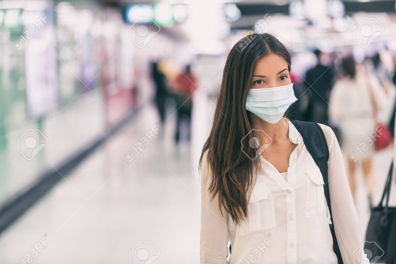 Coronavirus Asian woman walking with surgical mask face protection walking in crowds at airport train station work commute to hospital. - 139898510