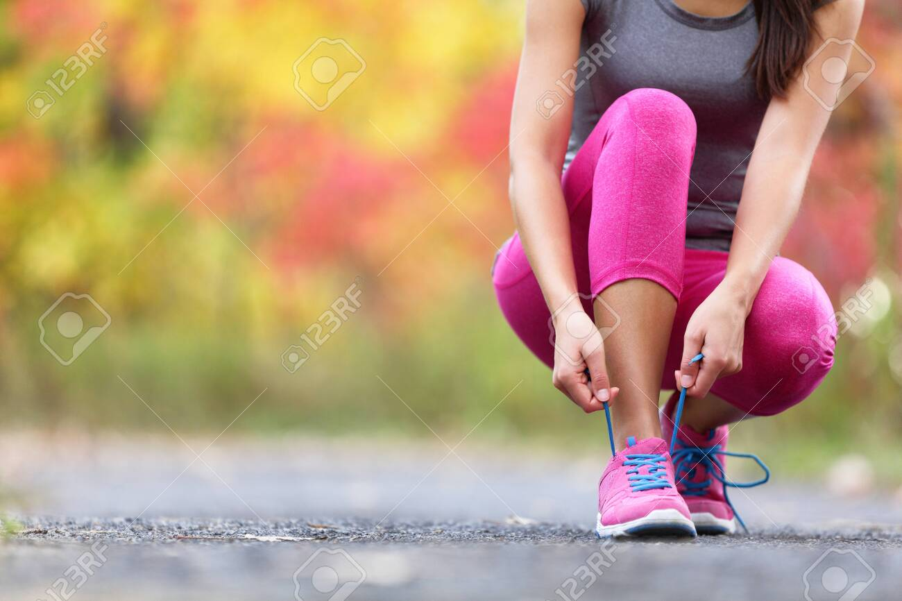 Autumn running shoes girl tying laces ready to run in forest foliage background. Sport runner woman training cardio in outdoor fall nature in pink activewear leggings and footwear. - 139898577