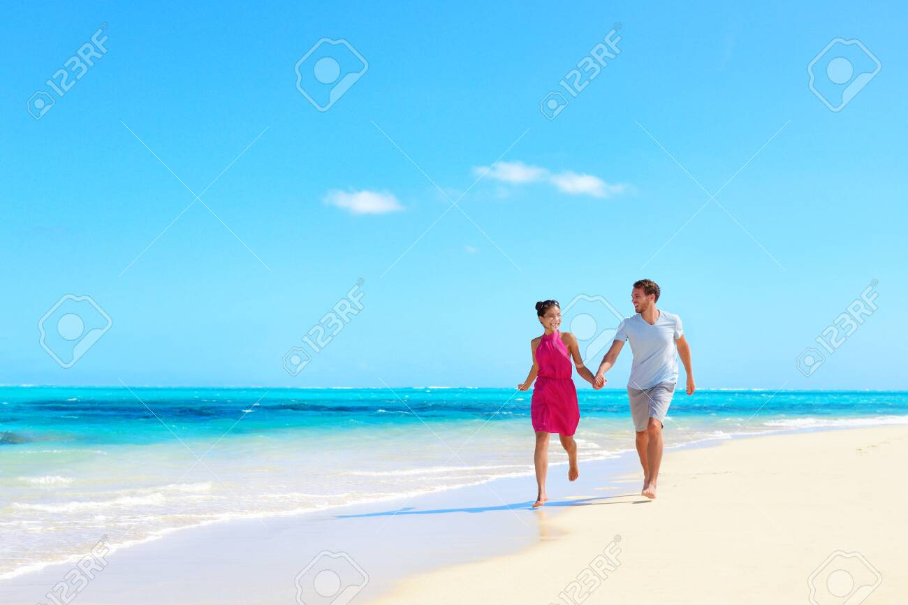 Beach vacation honeymoon paradise travel destination - Young couple in love walking holding hands in idyllic holiday background. - 139903700