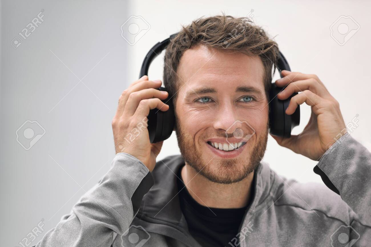 Music headphones man listening to audiobook online or songs on phone app. Happy smiling young person wearing wireless earphones. Young adult buying techonology wearable device at store. - 139907454