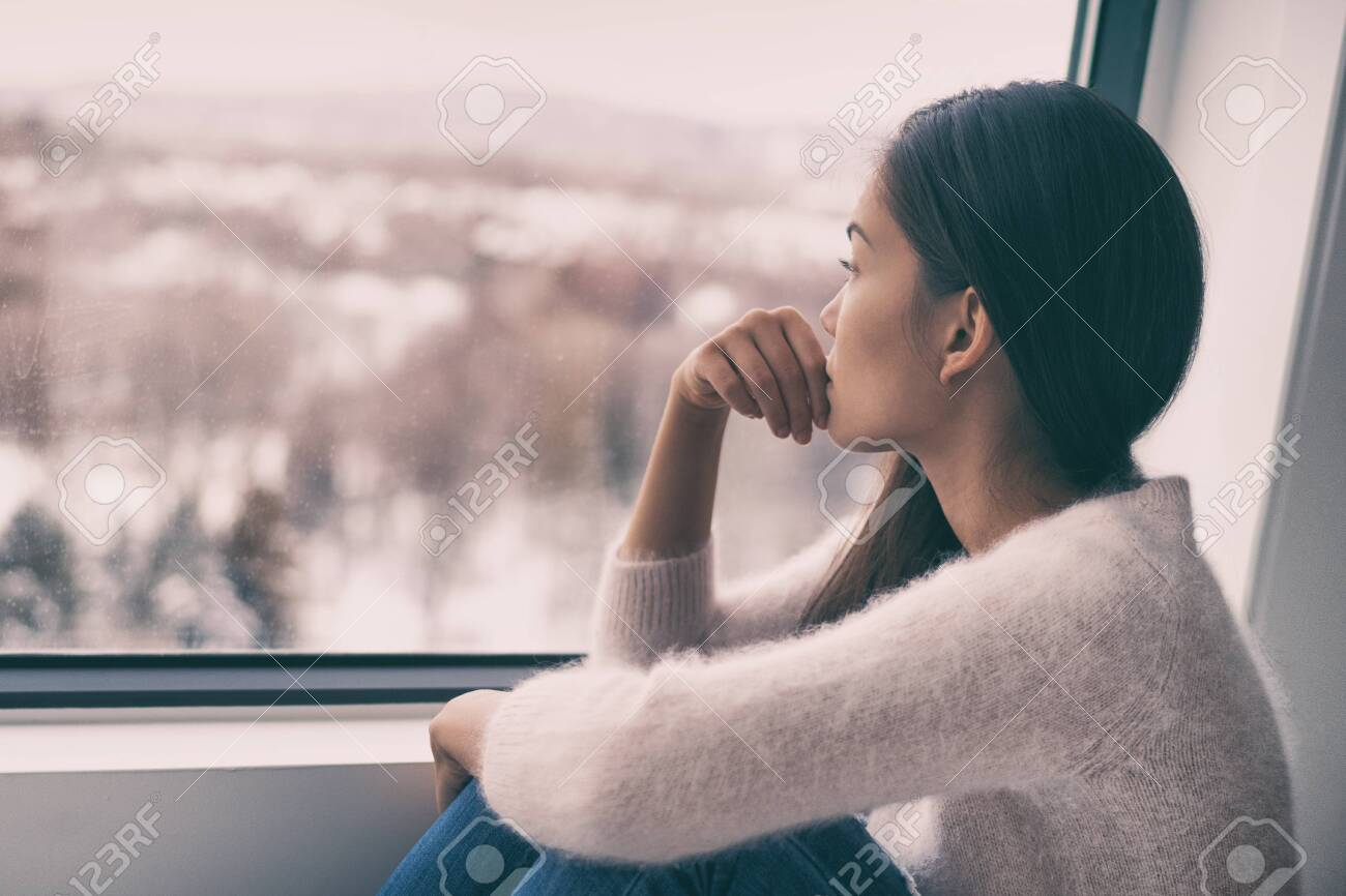 Winter depression - seasonal affective disorder mental health woman sad comtemplative looking out the window alone. - 141627002