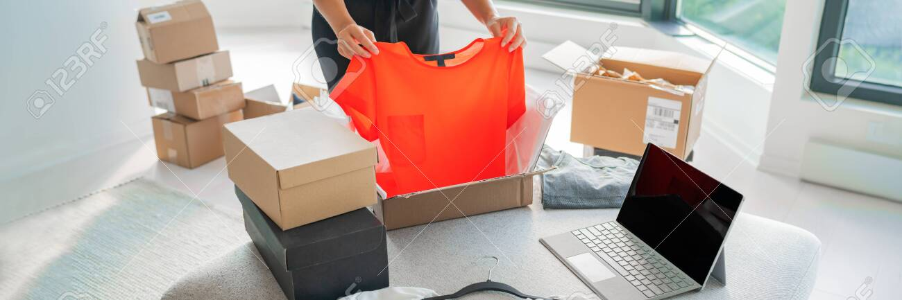 Online store selling clothes on website working on laptop ecommerce business from home. Woman packing new clothing fashion purchase in shipping packages for delivery. Panoramic banner. - 153411919