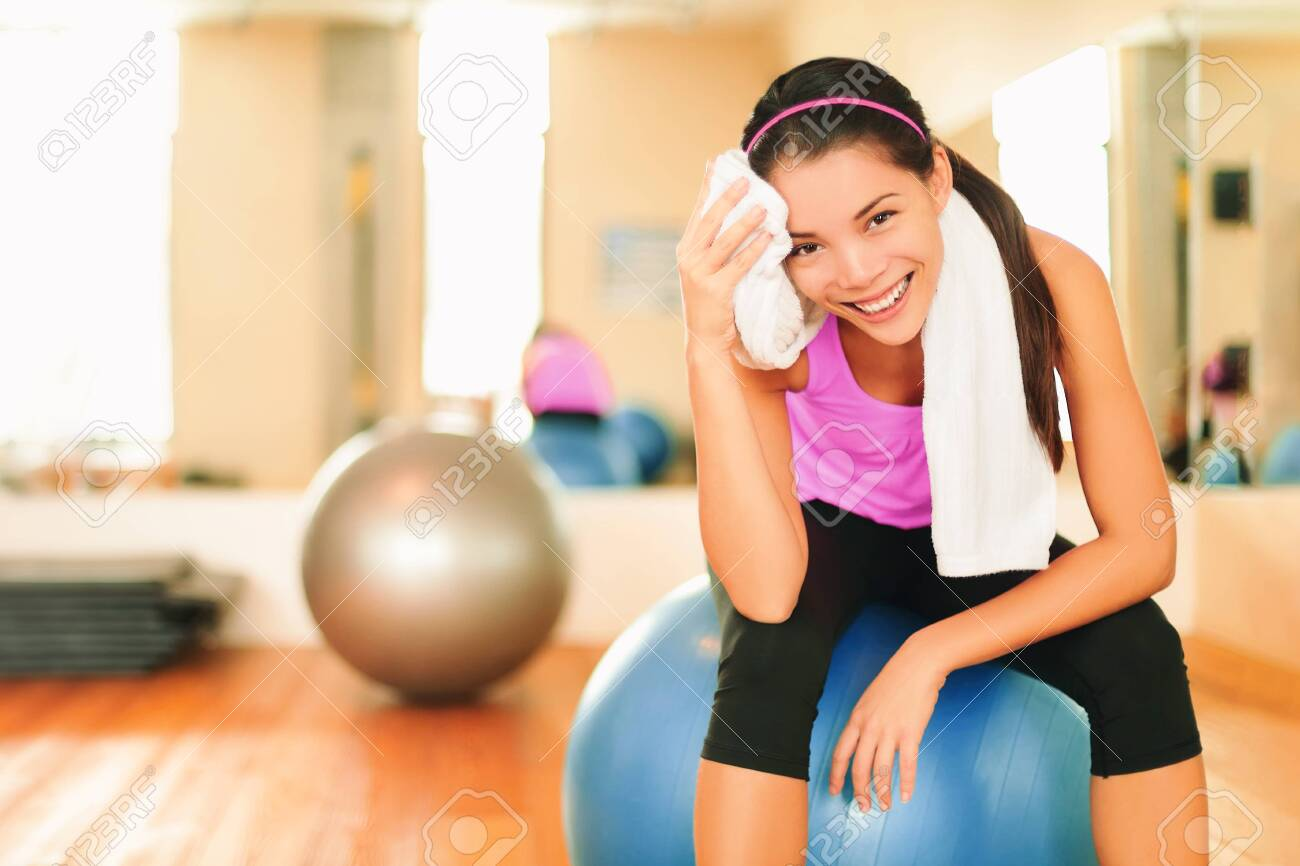 Asian fitness girl training at gym wiping sweat with towel post workout happy at gym. Exercise and healthy living weight loss concept. - 154450133