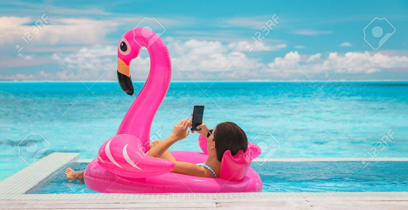 Relaxing woman floating in flamingo inflatable swimming pool toy at luxury resort using mobile phone sunbathing. Caribbean travel vacation hotel lifestyle. - 167171464