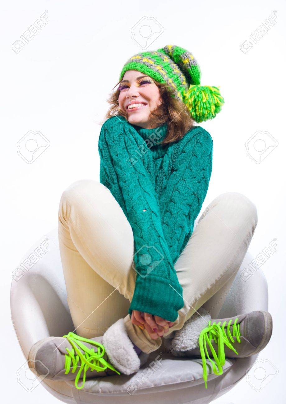 Cute funny girl wearing winter clothes like green knitted sweater and bright yellow hat with pom-pon, sitting on white chair, smiling and laughing with her eyes closed, hands and legs crossed. Isolated on white background. Copy space Stock Photo - 16935248