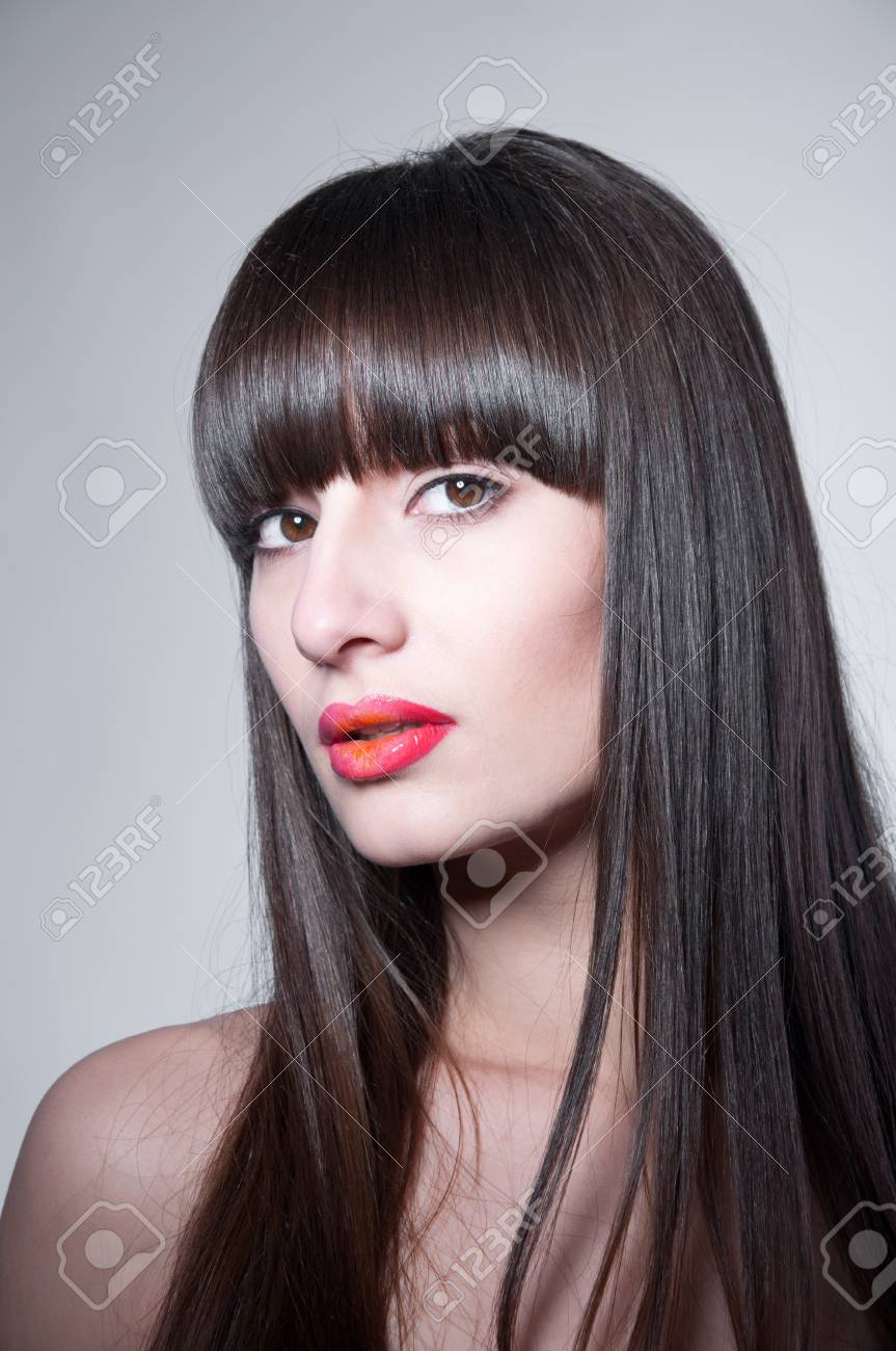 Beauty studio portrait of young pretty brunette female model with healthy long straight hair, long fridge, clear skin, elegant glamour makeup with slightly open glossy colorful red lips,  looking at camera. Copy space, gray background Stock Photo - 17644086
