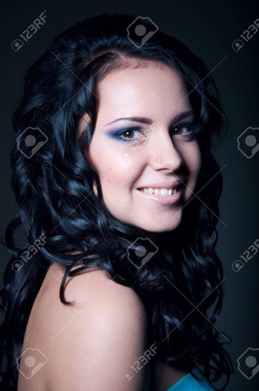 Studio portrait of pretty brunette woman model with naked shoulders, long shiny healthy black curly hair, elegant blue makeup, smiling and looking at camera. Gray black background Stock Photo - 17893565