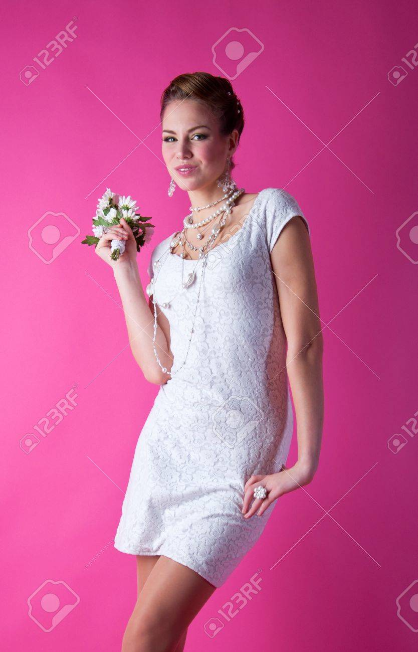 Pretty funny smiling bride girl wearing white lace wedding dress, pearls and beads, holding a bunch of flowers, having fun in studio and looking at camera with innocent but happy look against pink background Stock Photo - 18286623