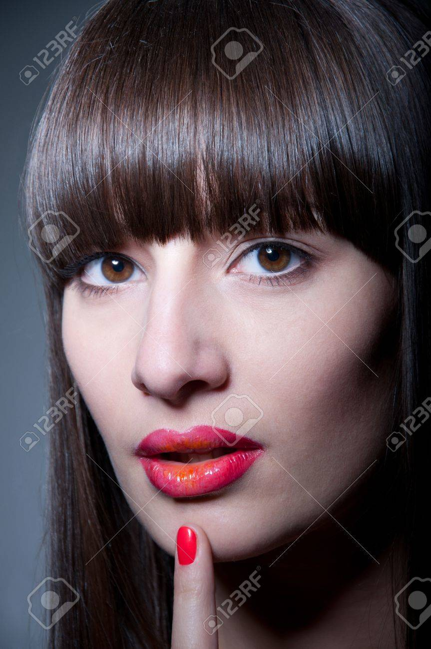 Beauty studio portrait of beautiful young woman model with long straight fringe, natural makeup, bright colorful red glossy lips and nail polish of the same color, holding her finger near lips, looking at camera. Gray background, copy space Stock Photo - 18346908