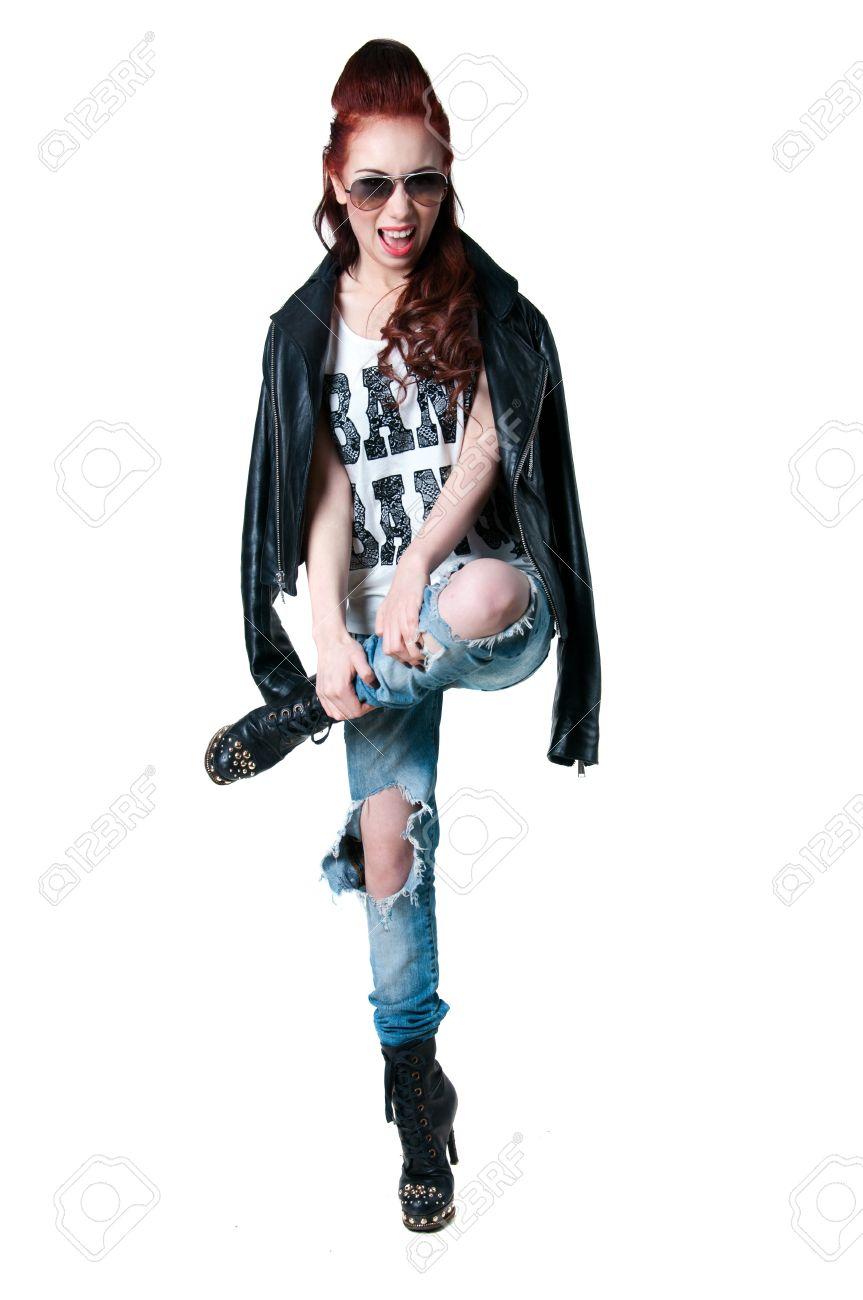 Mooie jonge rocker vrouw model met schattige rode kapsel, draagt lederen jas, spijkerbroek geript, zwarte laarzen met hoge hakken en spikes, met