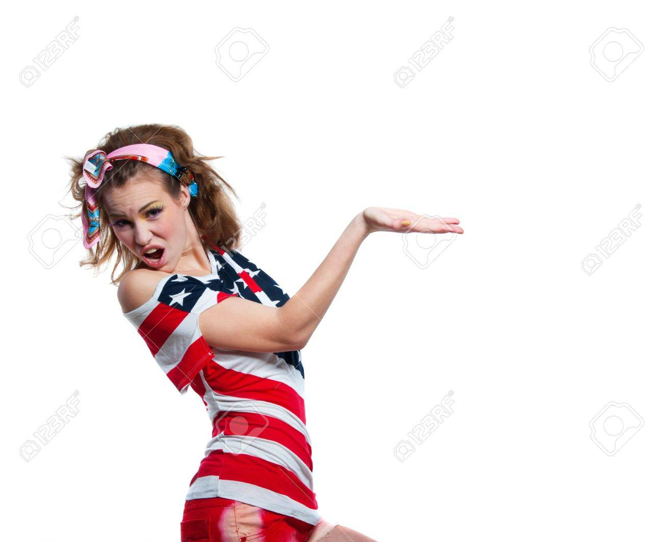 Beautiful young funny American patriotic girl wearing colorful pink blue head band, red shorts, off the shoulder top tank with USA flag, shouting loudly, pointing at something, smiling at camera. Isolated on white, copy space Stock Photo - 19938098