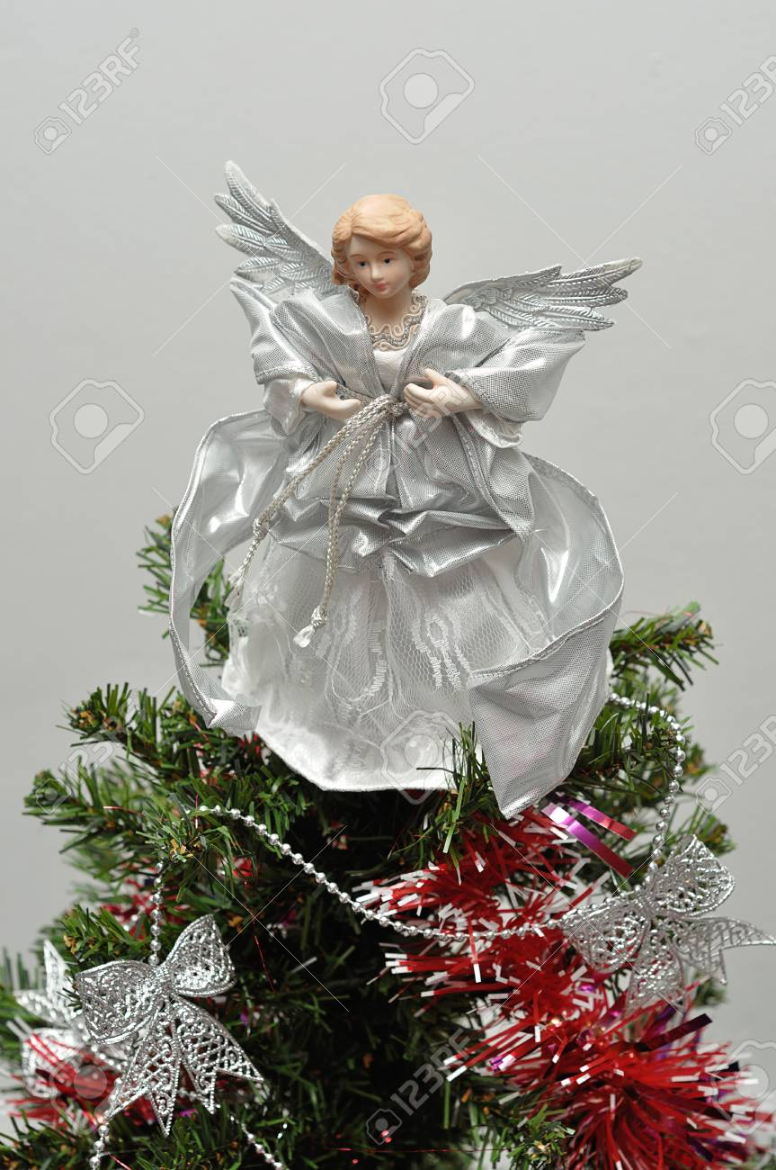 An Angel Tree Topper On Top Of A Christmas Tree Stock Photo Picture