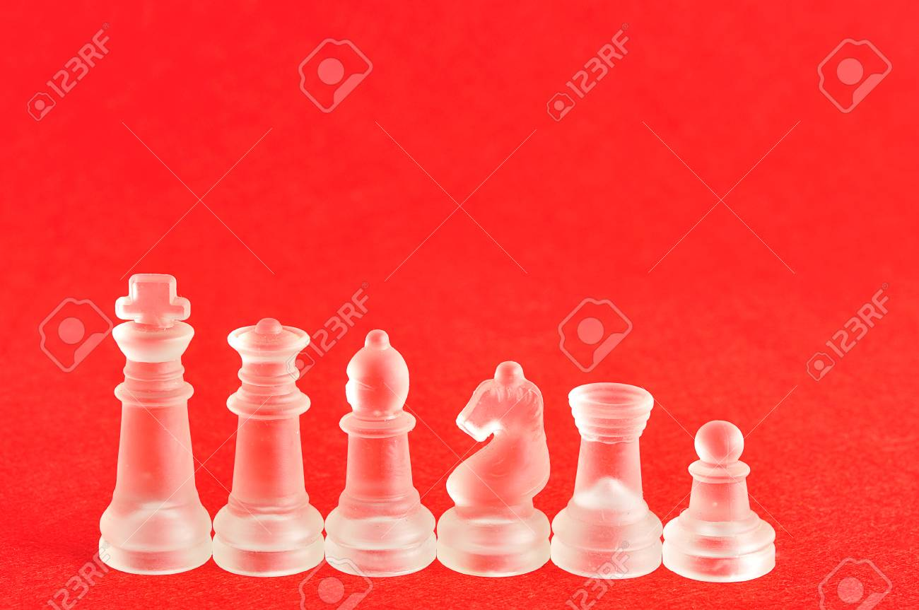 different chess pieces displayed on a red background stock photo