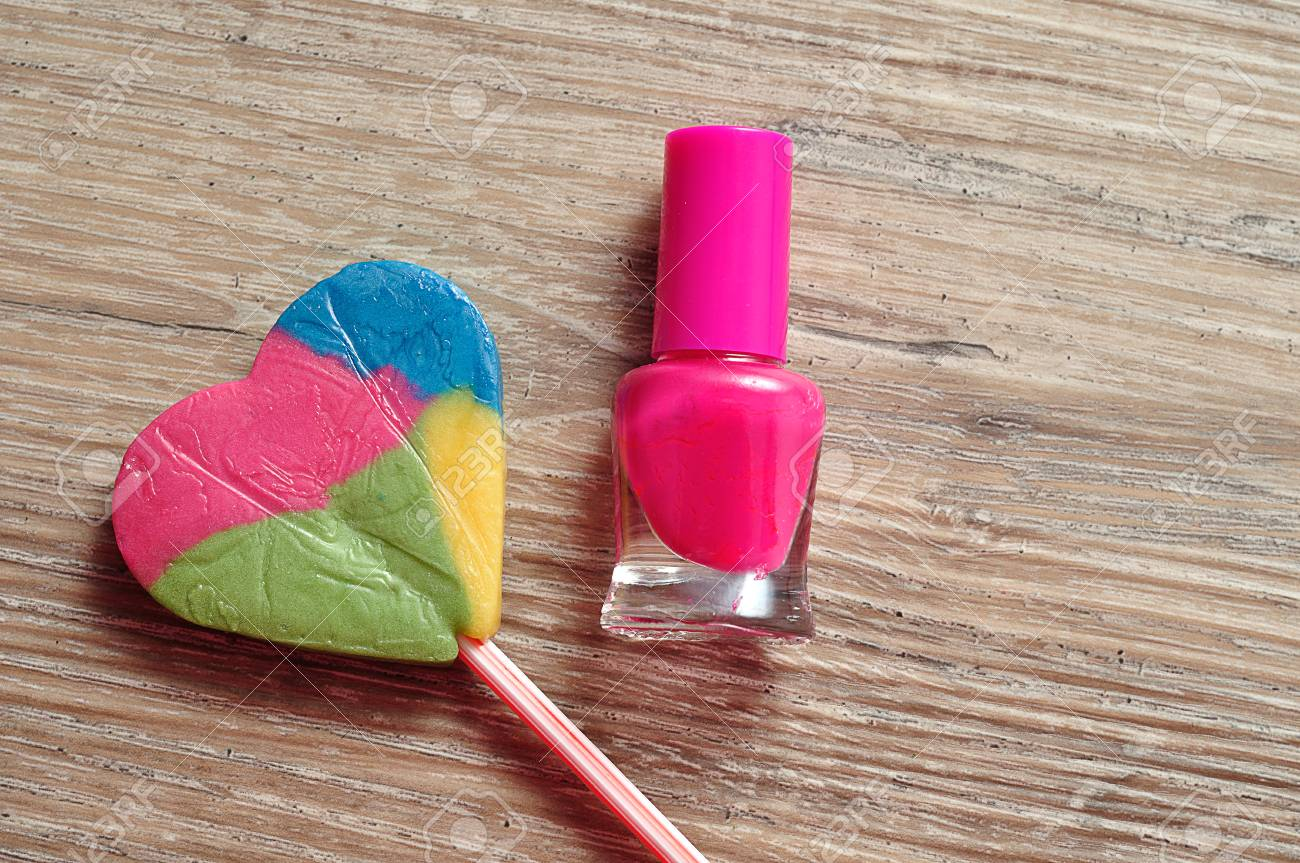 A Bottle Of Pink Nail Polish With A Colorful Heart Shape Lollipop ...