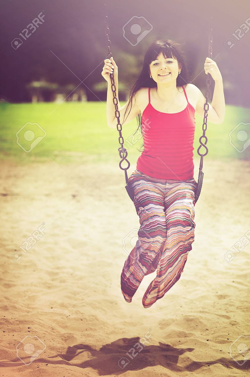 Young beautiful  woman on swing in summer sunny day Stock Photo - 13635804