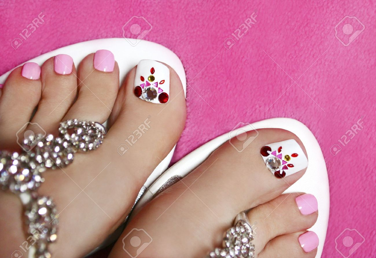 Pedicure on women s legs in a pink and white colour with rhinestones Stock Photo - 16466806