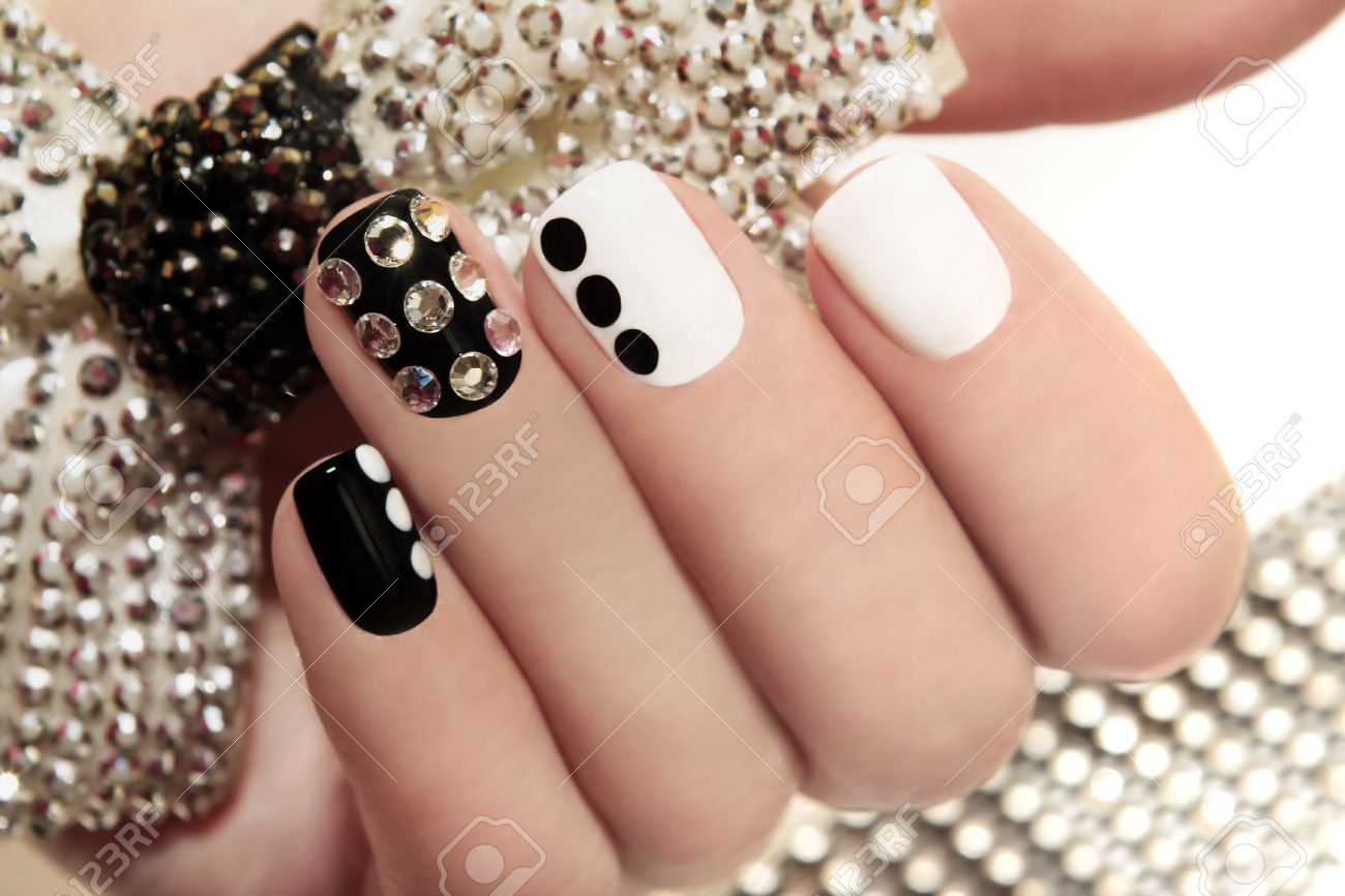 Manicure on short nails covered with black and white lacquered manicure on short nails covered with black and white lacquered with rhinestones on a black background prinsesfo Images