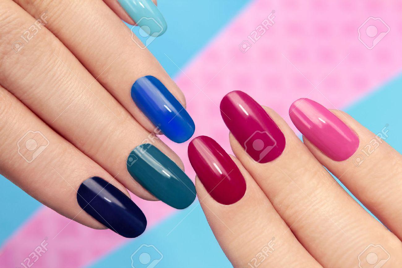 Banque dimages , Bleu rose vernis à ongles sur les ongles longs sur un fond coloré.