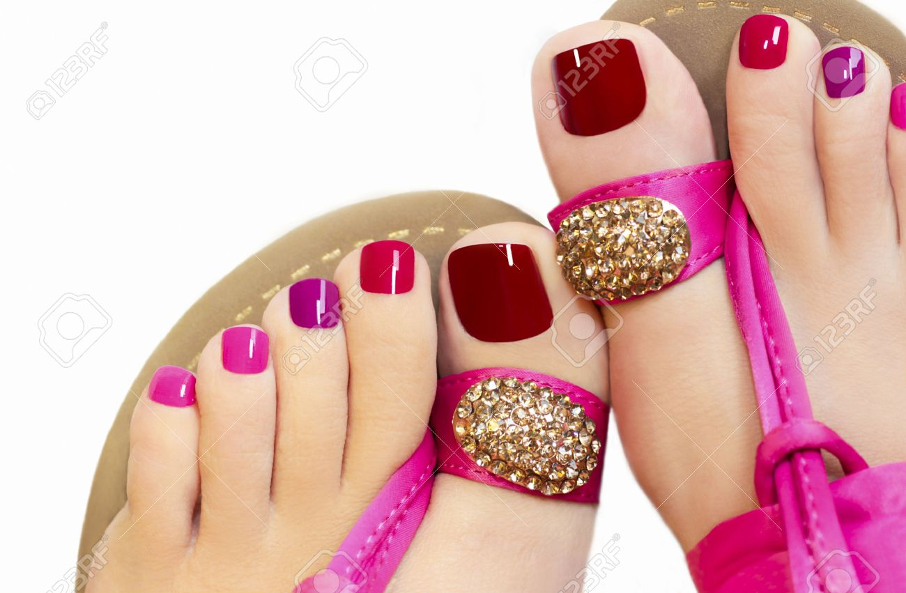 610777bf0840 Pedicure with different colors of paint on a woman s feet in pink sandals  on a green