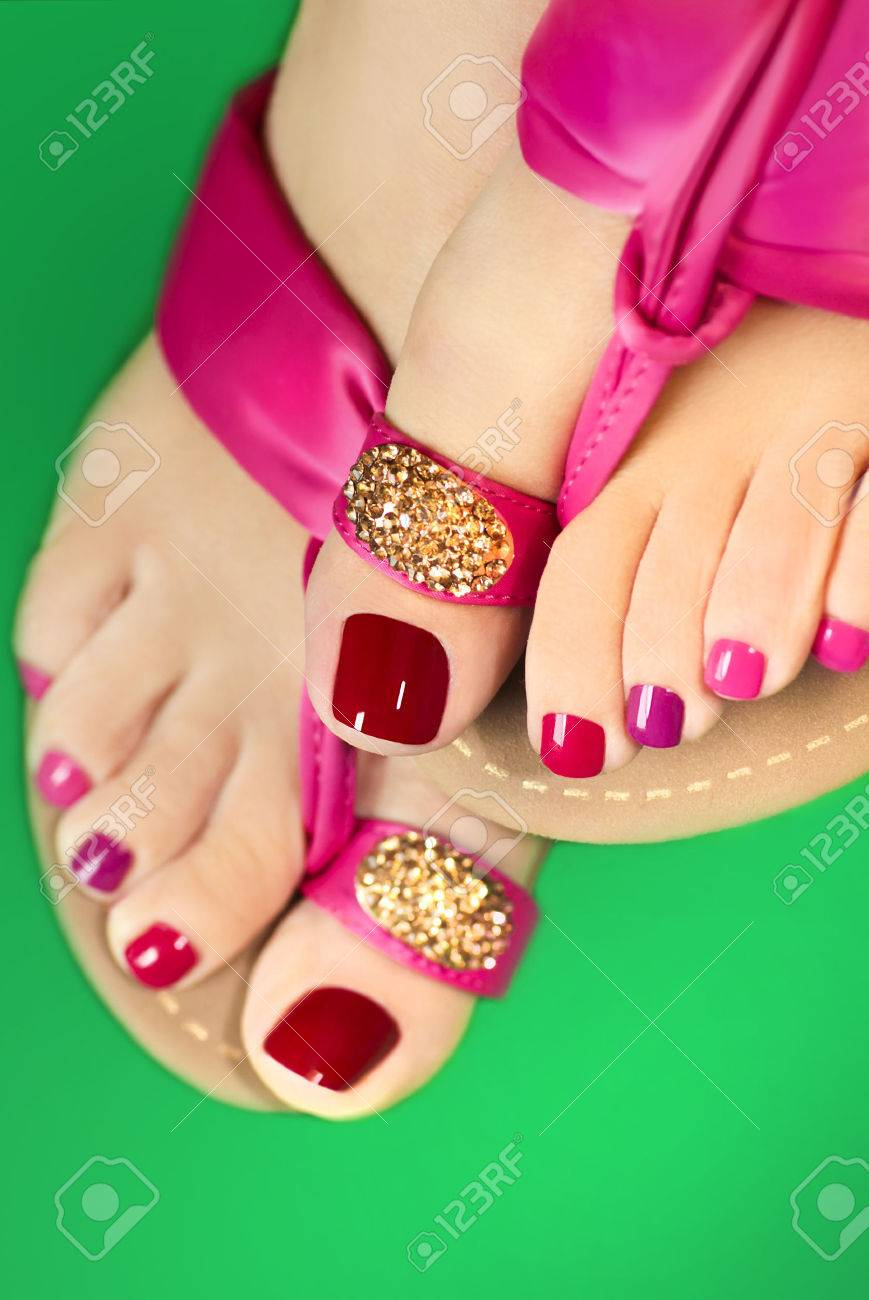 30ec3d73e130 Pedicure with different colors of paint on a woman s feet in pink sandals  on a white