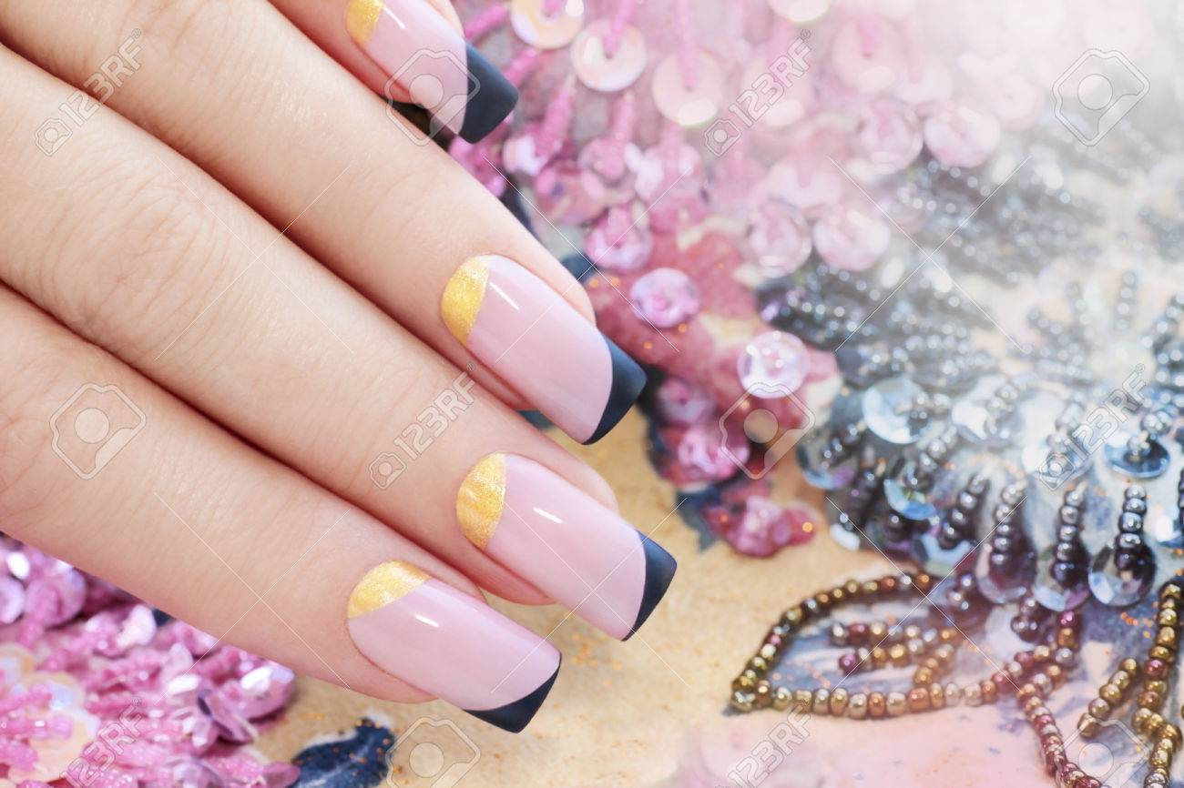 Pastel Pink Manicure With Black And Gold Nail Polish. Stock Photo ...