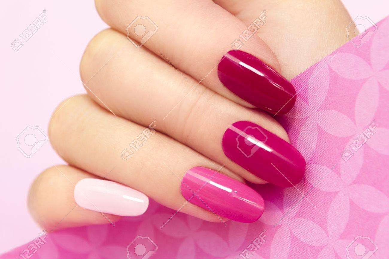 Manicura Multicolor Con Diferentes Tonos De Esmalte De Uñas De Color Rosa En La Mano De La Mujer