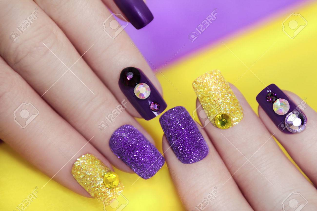 Lilac Purple Manicure With Gold Glitter And Rhinestones In Different Colors On A Background