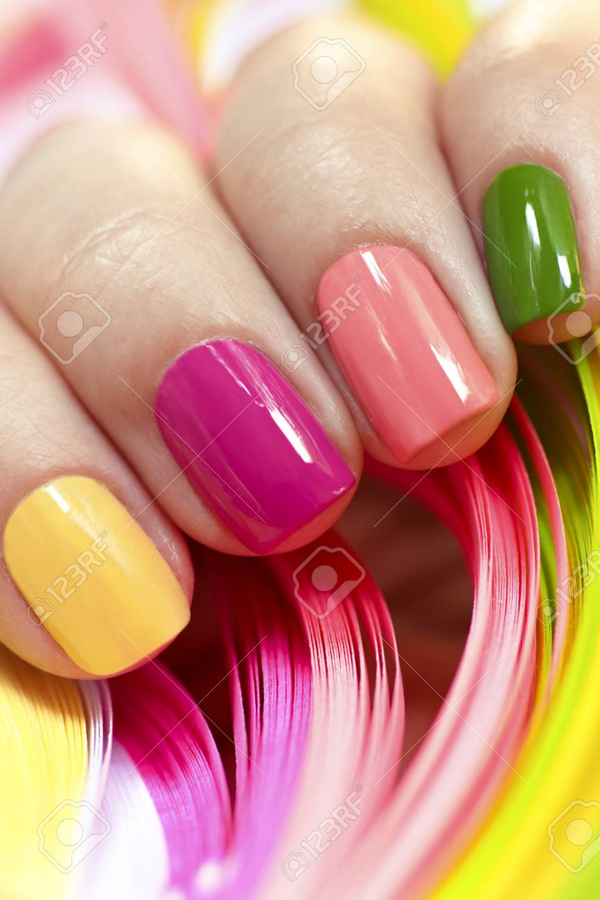 Multi-colored manicure with pink, green, yellow and peach nail..