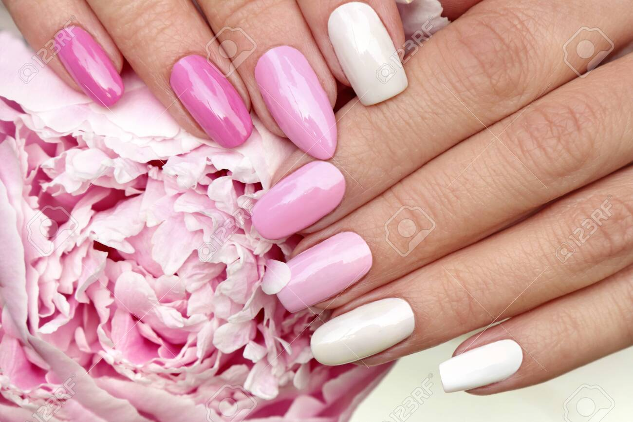 Light pink, pastel manicure on various shapes of nails with peony closeup. - 131921372