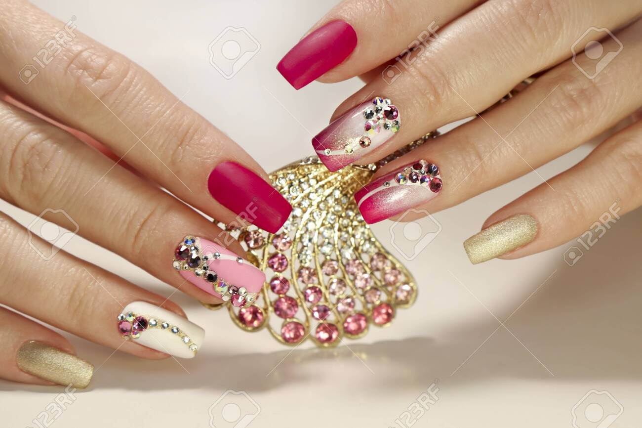 A luxurious manicure with a pink matte finish for nails and a gradient from white with gold to pink nail Polish. Nail art with various shaped rhinestones and colors. - 138830812