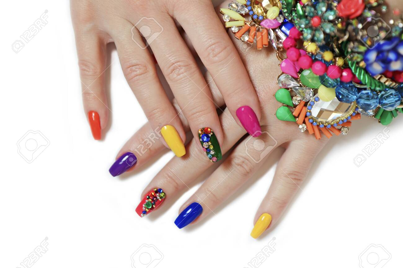 Creative bright saturated manicure on long nails with rhinestones. Nail art on women's hands on a white background with costume jewelry. - 143414174