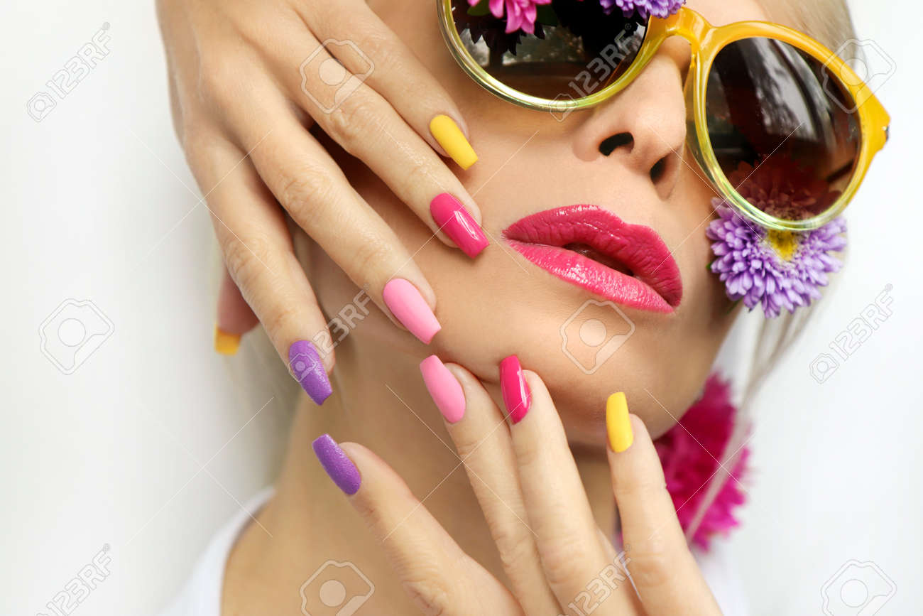Fashionable multi-colored makeup and manicure on long nails of a girl with asters and glasses. - 159195317